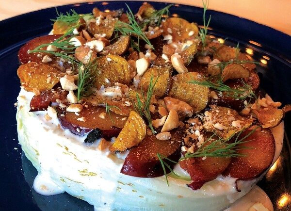 CLASSIC ICEBERG WEDGE: Frosted with a gorgonzola dressing, slices of grilled plums, candied beets, crumbled cashews, and sprigs of dill. Photo by Cliff Bostock.