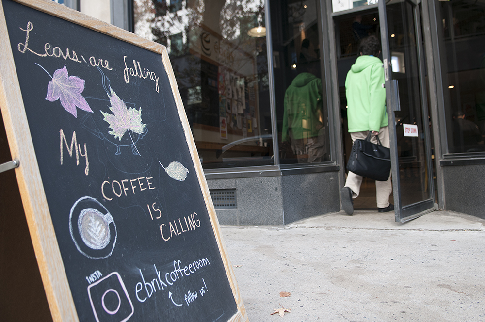 PICK-ME-UP: Ébrik charms people from the street with a cute chalkboard sign. Photo by Joeff Davis