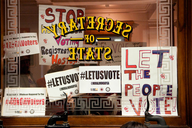 CAST A BALLOT: As protesters staged a sit-in inside the secretary of state's office on Oct. 27, additional supporters lifted signs to the window (left) and chanted,
